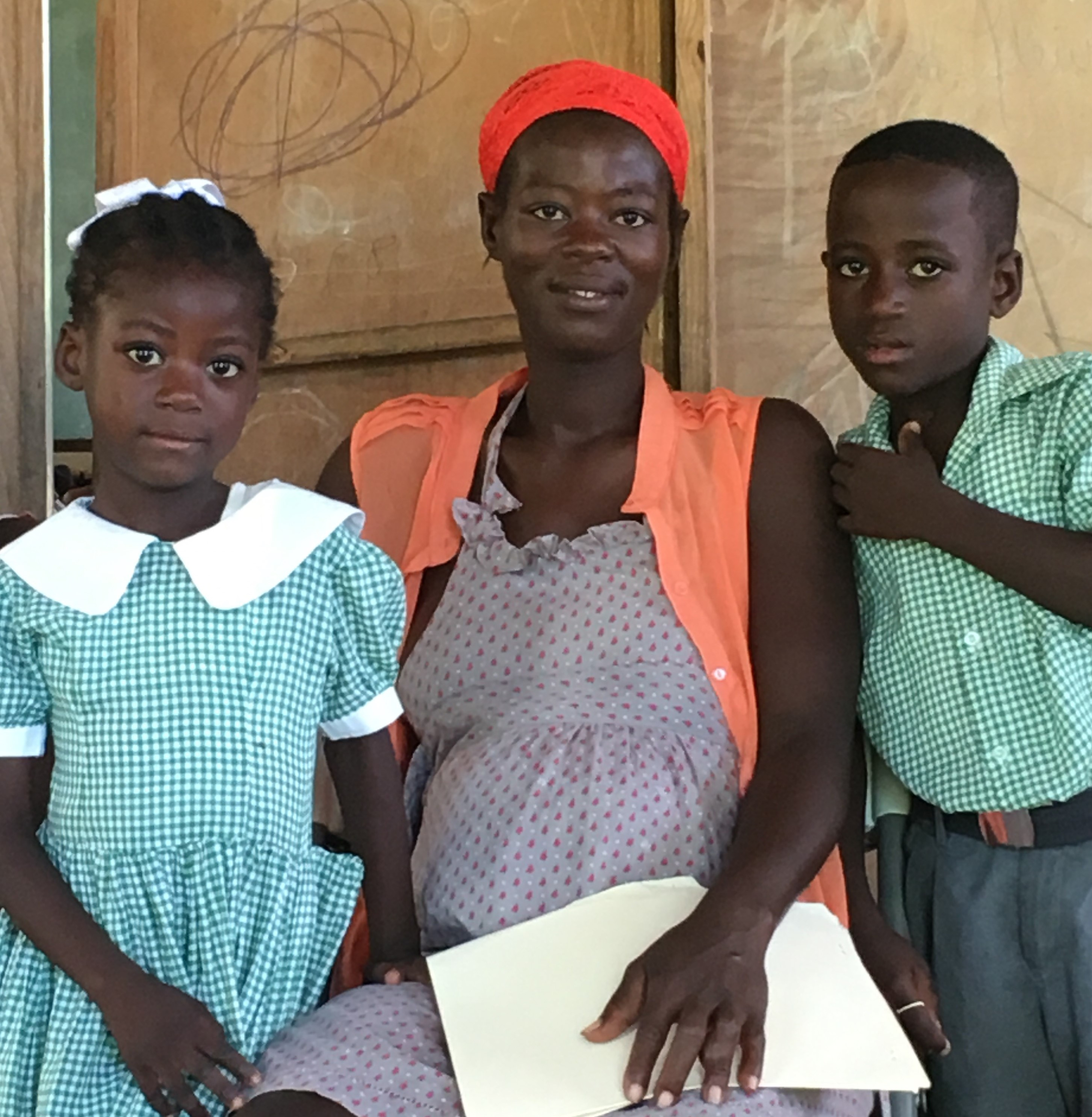 Haitian mom, Loulouse, with her son and daughter at a school clinic