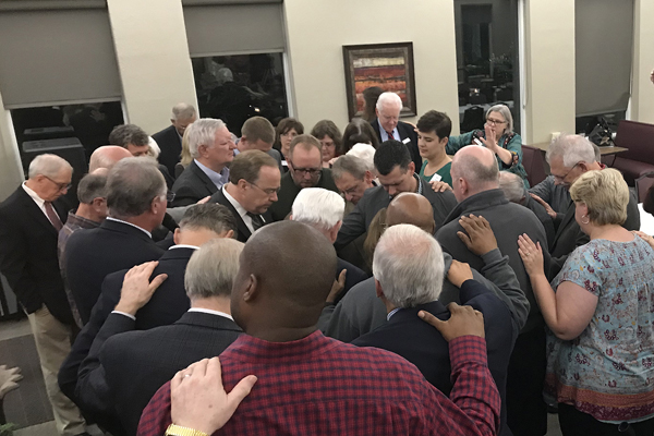 Board of Trustees, faculty and staff gather to pray following Dr. Rowell's election in October 20017