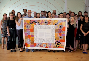 PIAC and other staff in a group with the Uluru statement from the heart