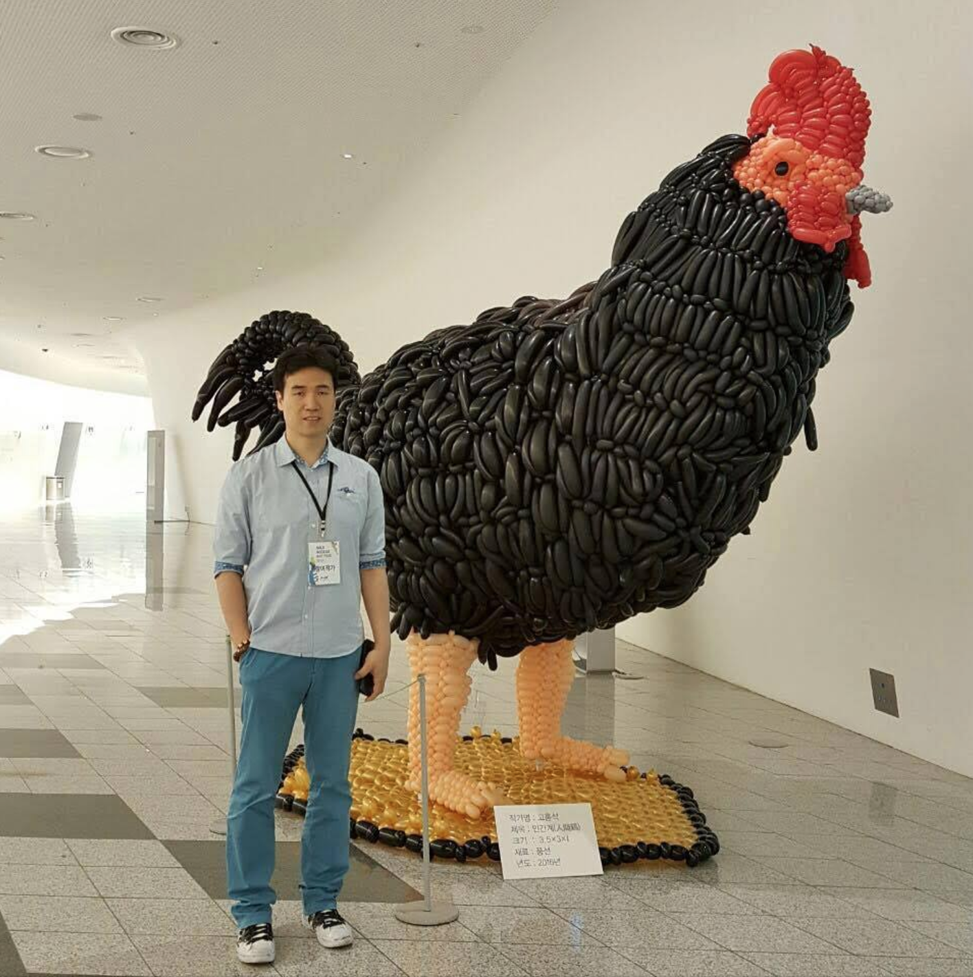 HongSeok Goh, blind artist, stands next to his sculpture made of balloons
