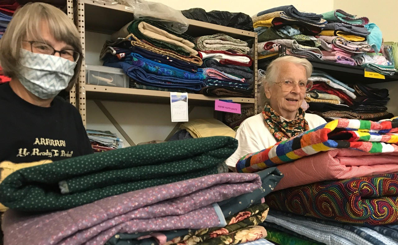 Fellow Community Service Guild Members Hold Quilts