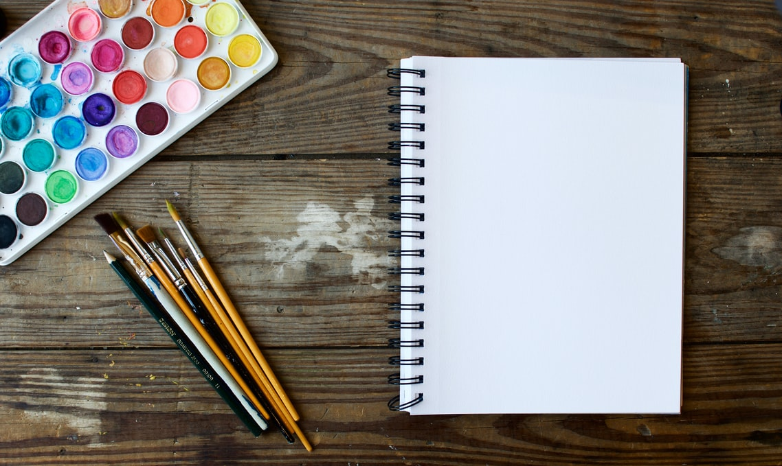Picture of a desk with paintbrushes, watercolour paints, and a blank sketchbook on it